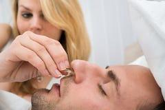 Vrouw die het apparaat van de neusklem opnemen in man neus stock foto