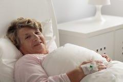 Vrouw die in het Bed van het Ziekenhuis ligt Stock Afbeelding