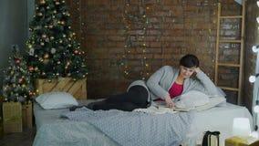 Vrouw die het Boek lezen dichtbij de Kerstboom stock video
