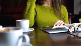 Vrouw die het boek lezen en koffie in een koffie drinken stock footage