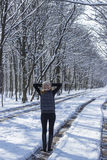 Vrouw die het bos in de winterdag overwegen Stock Afbeelding