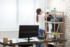 Vrouw die het Bureau schoonmaken royalty-vrije stock foto