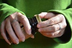 Vrouw die het deksel verwijderen uit een fles van pillen stock fotografie