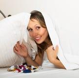 Vrouw die in het geheim suikergoed in bed eten stock fotografie