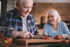 Vrouw die het glimlachen van man scherpe tomaten in keuken bekijken stock foto