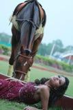 Vrouw die in het gras, dichtbij een weidend paard legt. Stock Fotografie