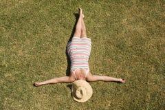 Vrouw die in het gras legt Royalty-vrije Stock Afbeeldingen