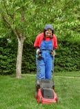 Vrouw die het gras snijdt Stock Foto's