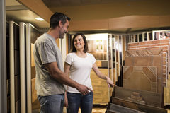 Vrouw die in het gunstigste geval ceramische vloertegel richten en bij de mens glimlachen stock afbeelding