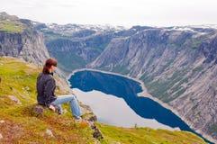 Vrouw die het meer in de bergen bekijken, Noorwegen Weg aan Trol Stock Foto