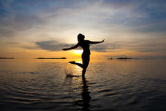 vrouw die in het ondiepe overzees bij zonsopgang danst Stock Foto's