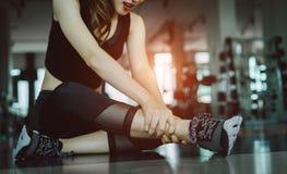 Vrouw die het ongeval van het de verwondingsbeen van de sportoefening doen stock foto's