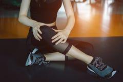 Vrouw die het ongeval van de de verwondingsknie van de sportoefening doen stock afbeeldingen