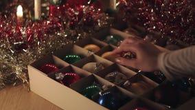 Vrouw die het oude uitstekende stuk speelgoed van het Kerstmisgebied nemen uit de doos stock video