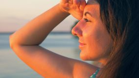 Vrouw die die het Overzees tijdens Zonsondergang bekijken van The Sun met Haar Hand wordt behandeld stock videobeelden