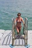 Vrouw die in het overzees van drijvende brug zwemmen Stock Afbeelding