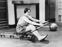 Vrouw die het roeien machine met behulp van Stock Foto's