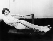 Vrouw die het roeien machine met behulp van Royalty-vrije Stock Afbeelding