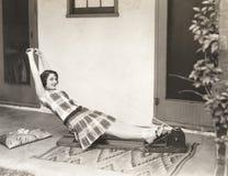Vrouw die het roeien machine thuis met behulp van stock afbeelding