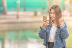 Vrouw die het slimme telefoon lachen en glimlach gebruiken royalty-vrije stock fotografie