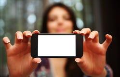 Vrouw die het smartphonescherm tonen Stock Foto's