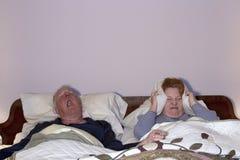 Vrouw die het Snurken aan Echtgenoot het hoofd bieden Stock Foto