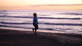 Vrouw die in het Strand bij Zonsondergang lopen Het concept van de geschiktheid stock videobeelden