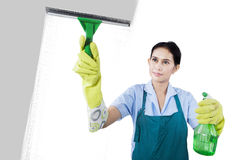 Vrouw die het venster schoonmaken stock afbeelding