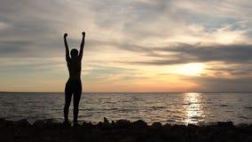 Vrouw die het vieren succes toejuichen bij strandzonsondergang stock videobeelden