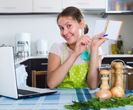 Vrouw die het winkelen lijst maken bij keuken Royalty-vrije Stock Afbeelding