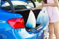 Vrouw die het winkelen zakken binnen boomstam van blauwe auto zetten Royalty-vrije Stock Afbeeldingen