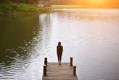 Vrouw die het zegevierende onder ogen zien op de brug in het meer voelen Stock Foto