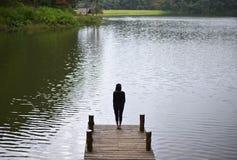 Vrouw die het zegevierende onder ogen zien op de brug in het meer voelen, Royalty-vrije Stock Foto's