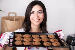 Vrouw die hete braadpan met koekjes houden Royalty-vrije Stock Foto