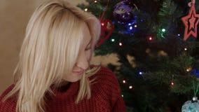 Vrouw die hete chocolade drinken onder de nieuwe jaarboom stock videobeelden