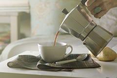 Vrouw die hete koffie in de woonkamer van zijn huis dienen Stock Foto's