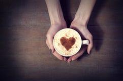 Vrouw die hete kop van koffie, met hartvorm houden Royalty-vrije Stock Afbeeldingen