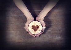 Vrouw die hete kop van koffie, met hartvorm houden stock afbeelding