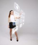 Vrouw die high-tech type van moderne knopen van verschillende media op een virtuele achtergrond drukken Royalty-vrije Stock Foto