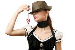 Vrouw die hoed draagt die hangend gevormd hart toont Stock Foto's