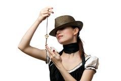 Vrouw die hoed draagt die hangende gestalte gegeven sleutel toont Royalty-vrije Stock Afbeelding