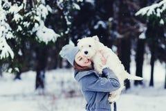 Vrouw die hond in een de winterdag koesteren stock afbeeldingen