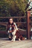 Vrouw die hond in park koesteren stock afbeeldingen