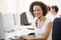 Vrouw die hoofdtelefoon in computerzaal draagt Stock Foto's