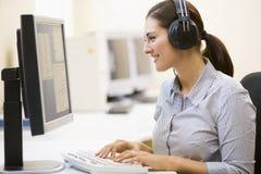Vrouw die hoofdtelefoons in computerzaal het typen draagt royalty-vrije stock foto's