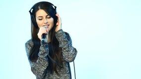Vrouw die hoofdtelefoons met microfoon het zingen dragen stock videobeelden