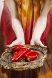 Vrouw die houten dienblad met rijpe roodgloeiende Spaanse peperpeper houden Stock Afbeelding