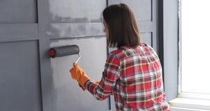 Vrouw die houten muur met rol schilderen stock videobeelden