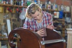 Vrouw die houten voorwerp in workshop oppoetsen stock afbeeldingen