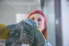 Vrouw die huishoudelijk werk doet Huisvrouw Portrait While Cleaning Foto door het glas royalty-vrije stock afbeeldingen
